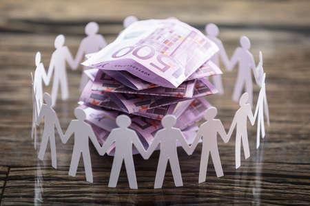 Nahaufnahme des Papiers herausgeschnittene menschliche Figur umgebenden Staplungsbanknoten auf Schreibtisch Standard-Bild