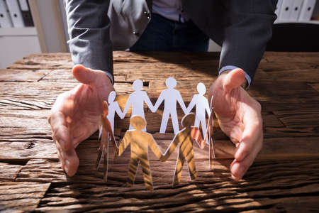 Businessperson's Hand Protecting Paper Cut Out Figures On Wooden Desk Stockfoto