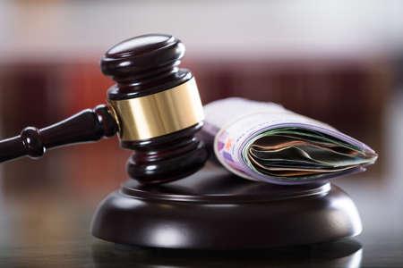 Nahaufnahme des Hammers und der Banknote im Gerichtssaal Standard-Bild