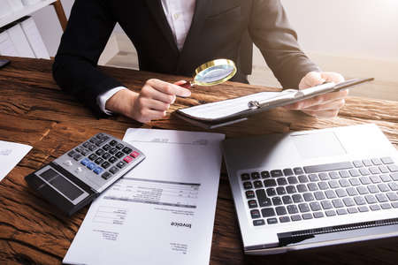 Businesspersons Hand Analyzing Bill With Magnifying Glass On Wooden Desk Stock Photo