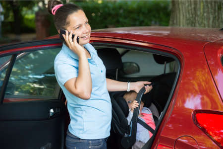 Happy Woman Standing Outside Car Talking On Mobile Phone