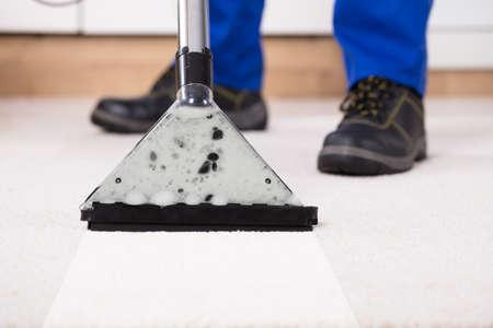 自宅でカーペットを掃除する掃除機を使った人のクローズアップ 写真素材
