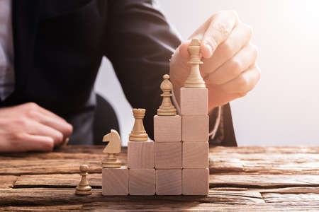Close-up Of A Businesspersons Hand Arranging Chess Piece On Wooden Blocks