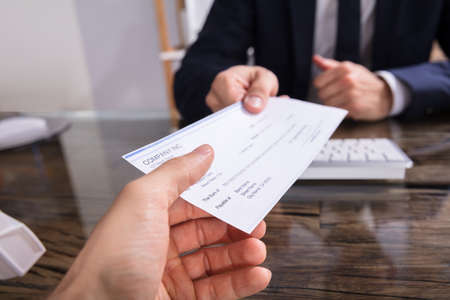 Close-up Of A Businesspersons Hand Giving Cheque To Colleague At Workplace
