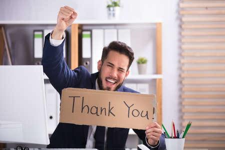 souriante jeune homme d & # 39 ; affaires levant les bras tout en tenant un carton avec le texte de remerciement