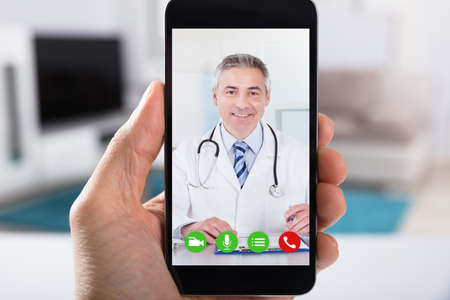 Close-up Of A Person Video Conferencing With Happy Male Doctor On Smartphone 免版税图像 - 93552794