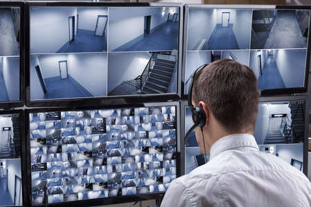 Rear View Of A Male Operator Wearing Headphone Looking At Multiple Camera Footage On Computer