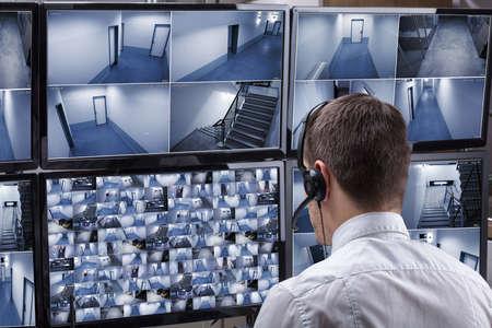Widok z tyłu męskiego operatora noszącego słuchawki patrząc na nagrania z wielu kamer na komputerze