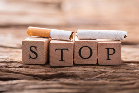 Close-up Of A Cigarette And Wooden Blocks Showing Stop Word On Desk