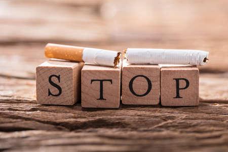 Gros plan, a, cigarette, et, blocs bois, projection, stop, mot, sur, bureau