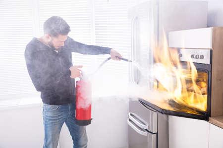 Giovane che per mezzo dell'estintore rosso per fermare l'incendio che viene dal forno in cucina Archivio Fotografico - 93523283