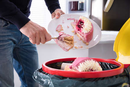 Close-up Of A Human Hand Throwing Cake In Trash Bin