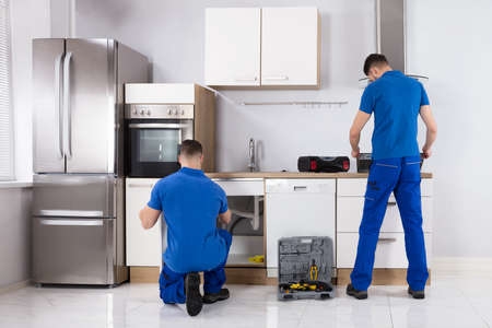 Rear View Of Two Men Checking Induction Stove And Sink Pipe In Kitchen