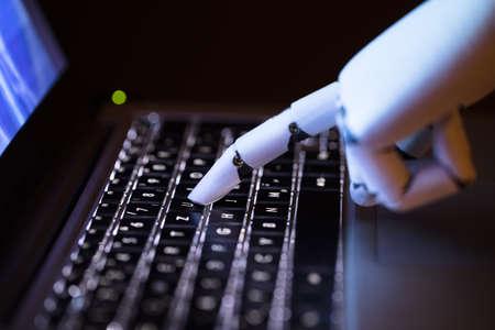 Primo piano della mano di un robot che digita sul computer portatile Archivio Fotografico - 93313718