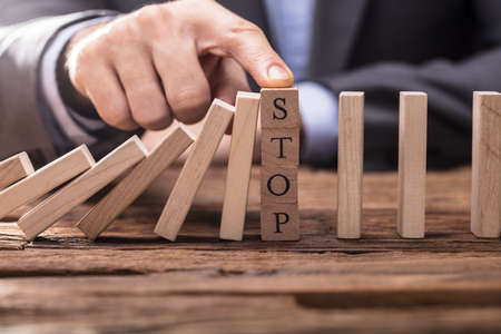 Businesspersons Finger Halting Dominos Effect By Placing The Finger On Wooden Stop Block Stock Photo