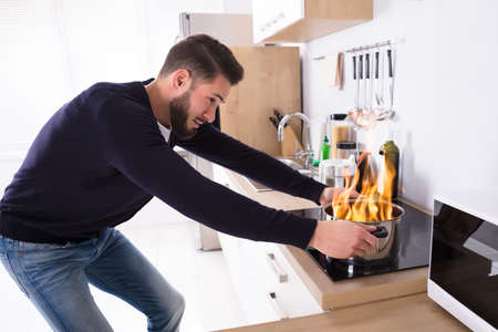 Side View Of A Young Man Holding Utensil On Fire In Kitchen Stock Photo