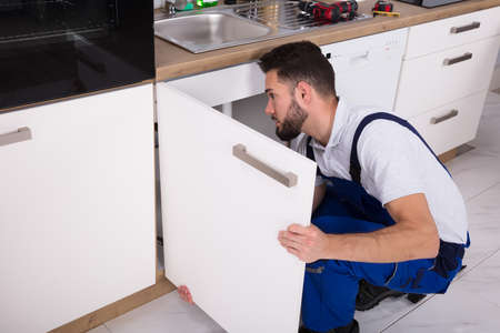 Young Handyman Fixing Sink Door In Kitchen