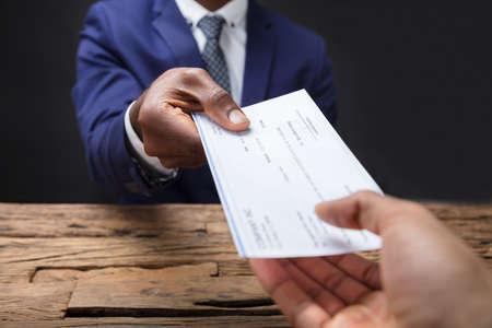 木製の机の上に同僚に小切手を与えるビジネスマンの手のクローズアップ
