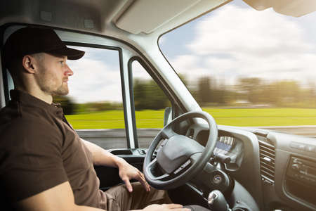 Portrait Of A Young Delivery Man Sitting Inside Self Driving Van