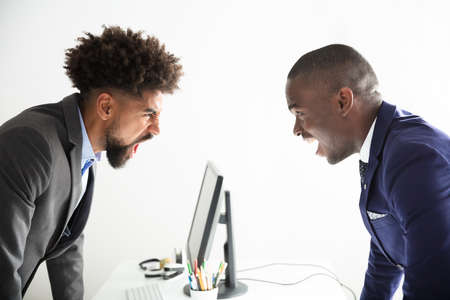 Two Angry Young Businessmen Shouting At Each Other At Workplace Stock fotó