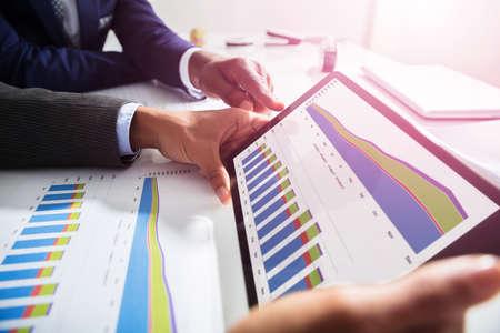 Close-up van Twee Zakenlui die met Financiële Grafiek aan Digitale Tablet samenwerken