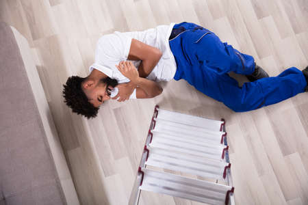 Young Handyman Falling From The Ladder In The Living Room Got Hurt On His Arms