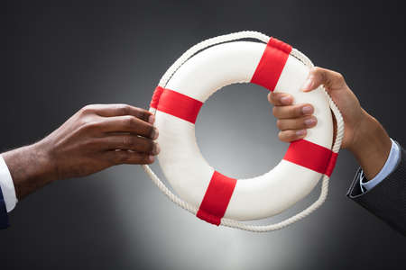 Businesspeople Holding A Lifebuoy In Hands On Gray Background