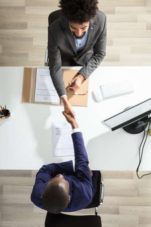 Erhöhte Ansicht der jungen Geschäftsmann Hand Hand mit männlichen Kandidaten über weißen Schreibtisch