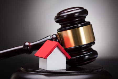 Close-up Of Gavel And House Model On Sounding Block Against Grey Background Stock Photo