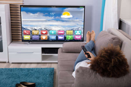 Vrouw liggend op de bank televisie kijken met kleurrijke toepassingen op het scherm