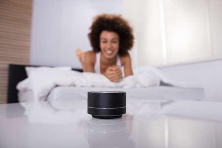 Lächelnde junge Frau, die auf Bett liegt, das Musik auf drahtlosem Lautsprecher hört