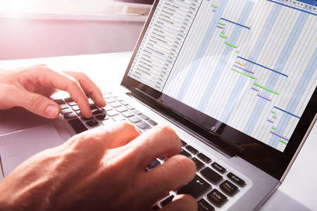 Close-up Of Businessmans Hands Working On Gantt Chart On Laptop At Office