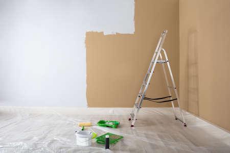 Hälfte gemalte weiße Wand mit Leiter und Malereiausrüstungen zu Hause Standard-Bild - 93769315