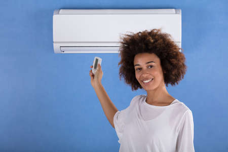 Young Woman Adjusting Air Conditioner Mounted On Blue Wall With Remote Control Stock Photo