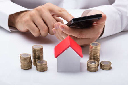 Businessman Using Calculator With Stacked Coins And House Model On Desk
