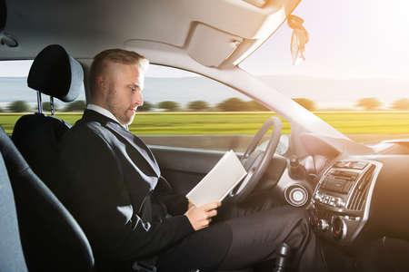 joven hombre de negocios sentado dentro de la conducción de coches y libro de lectura Foto de archivo