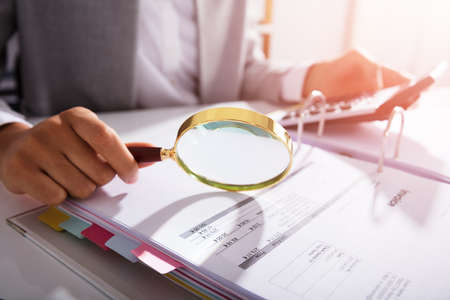 Photo Of Businesswoman Analyzing Invoice With Magnifying Glass Banque d'images