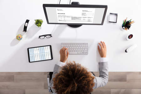 Businessperson Working On Computer With Invoice On Computer Screen In Office