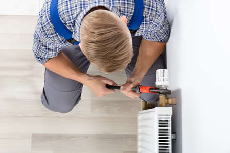 Close-up Of Male Plumber Fixing Thermostat Using Wrench At Home Stock Photo