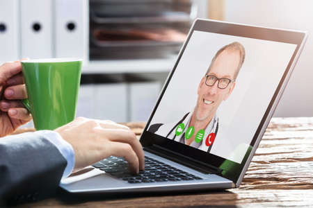 Close-up Of A Persons Hand Video Conferencing With Smiling Male Doctor On Wooden Desk