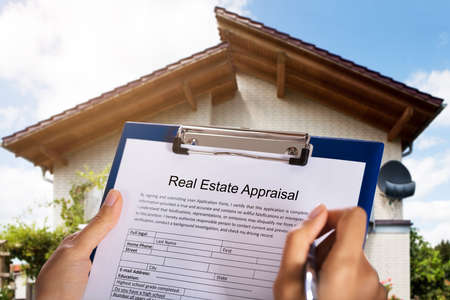 Person Filling Real Estate Appraisal Form In Front Of House Foto de archivo