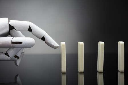 Robotic Hand Pushing Dominos On Grey Background