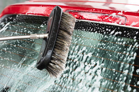 Close-up Of Persons Hand Washing Car Using Broom