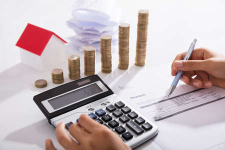 Businessperson Calculating Invoice With Stacked Of Coins In Office