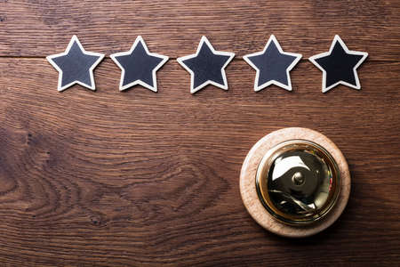 Elevated View Of Black Five Stars Arranged In Row With Service Bell On Wooden Desk