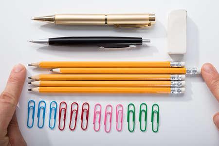 Der Finger der Person, der die Bleistifte mit Reihe des Stiftgummis und -stiftes auf weißem Hintergrund anordnet Standard-Bild