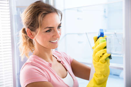 Young Woman Wearing Gloves Cleaning Refrigerator With Spray Bottle And Sponge Stock Photo