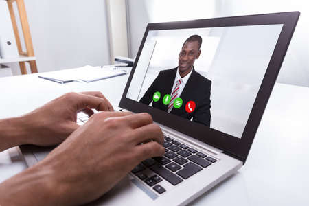 Close-up Of A Businessperson's Hand Video Conferencing With Male Colleague On Laptop At Workplace