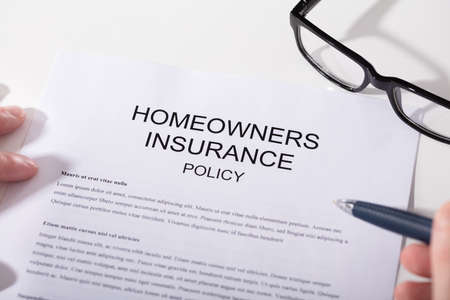 Close-up Of Homeowners Insurance Policy Form And Spectacles