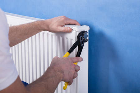 Close-up Of A Human Hand Installing Radiator With Wrench